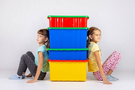 Two girls from different sides leaned their backs on plastic boxes