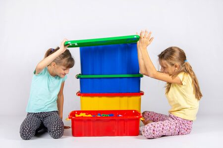 Two girls opened the lid of a large plastic box with toys, and look inside
