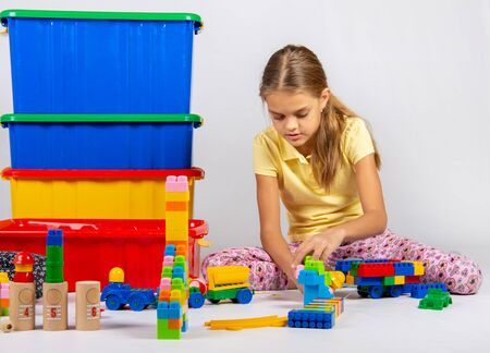 Ten year old girl playing toys sitting on the floor