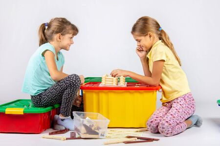 Two girls collect a house on a box with toys
