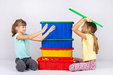 A girl pretending to be a hundred wants to throw a toy box lid on another girl