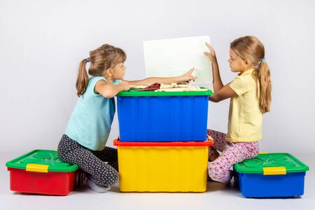 Two girls sit on large toy boxes and look at the toy assembly instructions