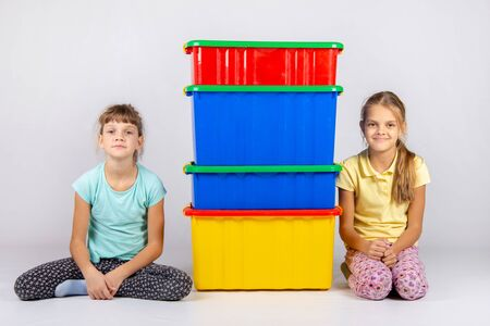 Zwei Mädchen sitzen neben vier großen Plastikkisten