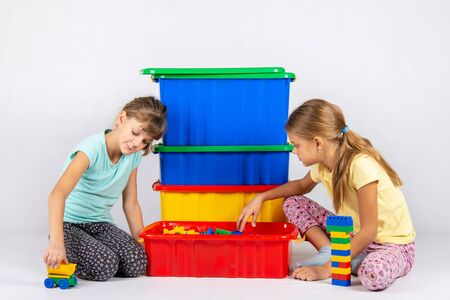 Two girls opened a box with a designer and start to play toys