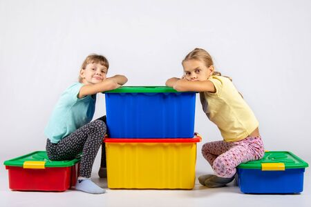 Two girls are sitting on large boxes for toys and looked into the frame