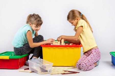 Two girls are assembling a house on a box with toys, looking in the instructions Reklamní fotografie