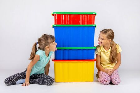 Two girls peek from different sides of large plastic boxes and show each other their tongues Reklamní fotografie