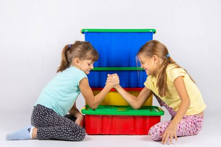 Two girls fight on hands, putting elbows on a box with toys Banque d'images