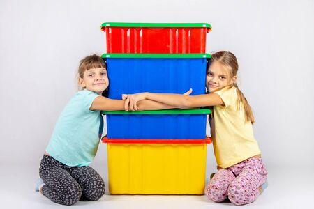 Two girls hug big plastic boxes Reklamní fotografie
