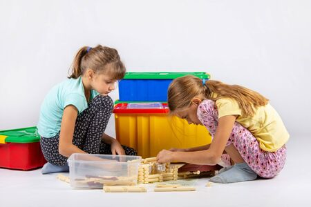 Two girls sit on the floor and collect a toy house