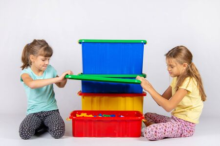 Two girls opened a large plastic box with toys