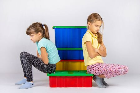 Two girls quarreled, sit on a box and turned away from each other
