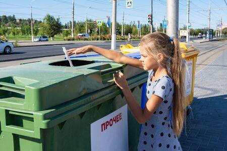 Girl throws a napkin into the trash bin