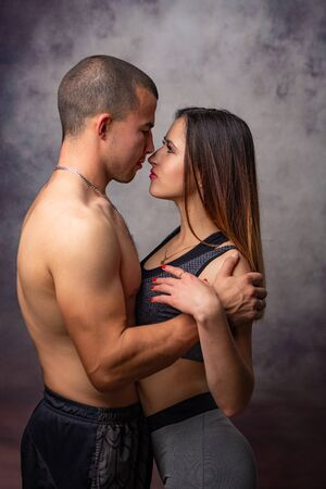 Girl and guy of athletic physique in sports clothes hug each other