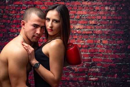 Young boxer and his girlfriend against the red wall