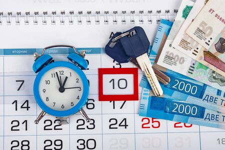 The calendar is allocated number 10, there is an alarm clock, money and keys to the apartment Stock Photo
