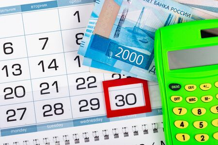 Calendar with a allocated 30 number, Russian two two-thousand bills, calculator