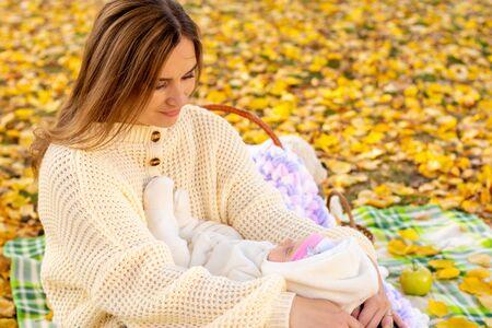 La mamma guarda amorevolmente il bambino mentre si siede per un picnic nel parco