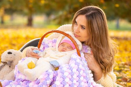Mom relaxes with newborn baby in park