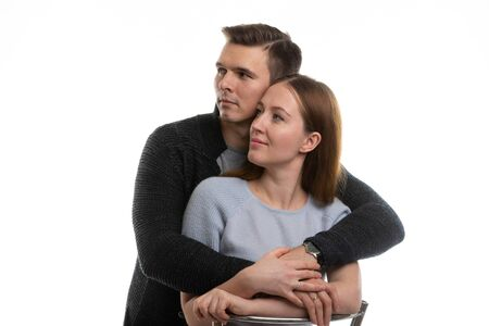 Portrait of a young couple looking to the left, a white background