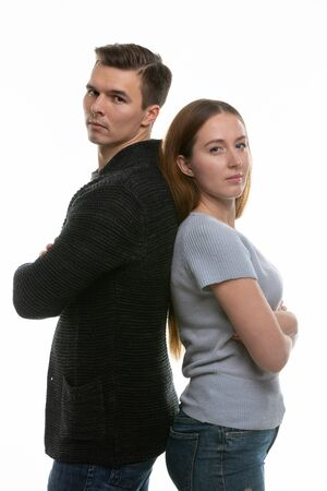 A couple with big problems stand with their backs to each other and look into the frame