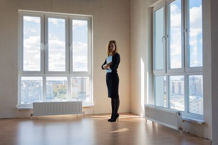 Realtor expects buyers in a large room with huge windows