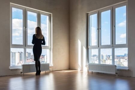 A girl looks into large stained glass windows in an empty apartment