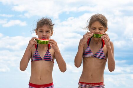 Two girls eat watermelon on the beach against the cloudy sky