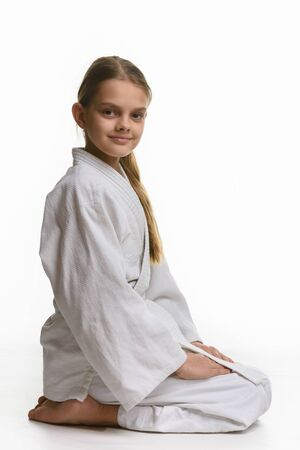 Girl in judo class, sitting on the floor, the view from the side