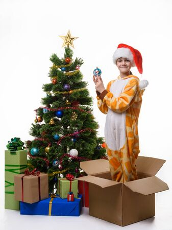 The girl stands in a box of Christmas tree toys dressing up the Christmas tree and looked cheerfully in the frame