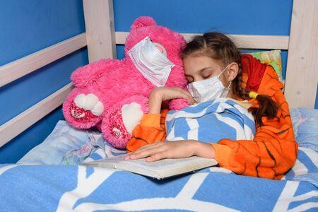 Sick girl in medical mask fell asleep in bed Reklamní fotografie