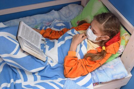 The sick girl went to bed to read a book and for a while removed the medical mask Stock Photo