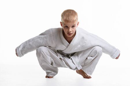 Martial arts student dressed in a kimono performs a squat Stockfoto