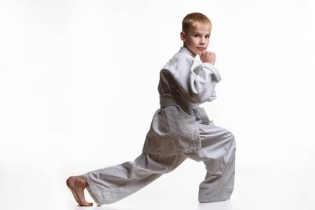 Martial arts student crouches, stretches his legs and looked into the frame
