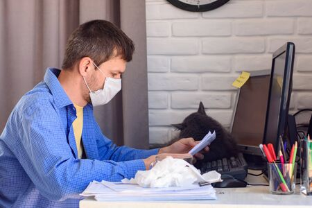A man in a medical mask reads a document while working remotely