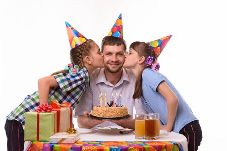 Children congratulated father on his birthday and kiss him on the cheek