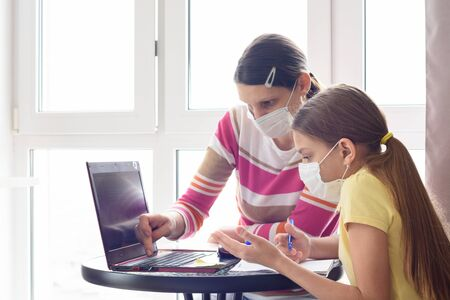 Mom and daughter in self-isolation regime go through online schooling