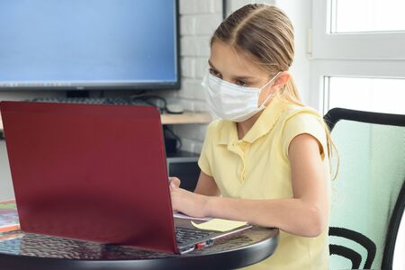 A girl in a medical protective mask undergoes distance learning
