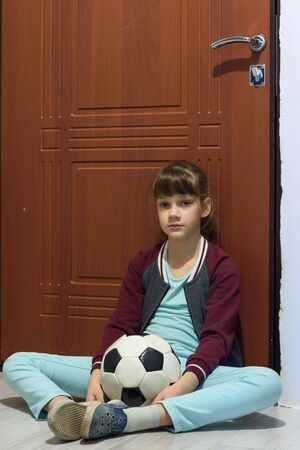 A girl with a ball sits at the door and is sad