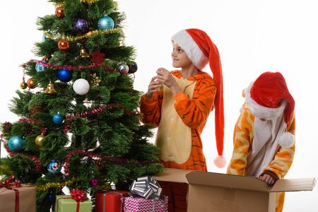 Girls decorate a Christmas tree, one of them delves into a box with toys