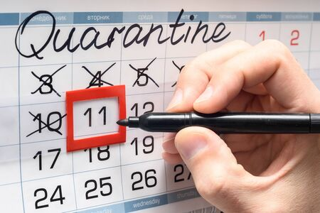 A hand crosses out the next day on the calendar during the quarantine period
