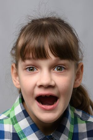 Portrait of a genuinely surprised ten-year-old girl with closed eyes, European appearance, close-up