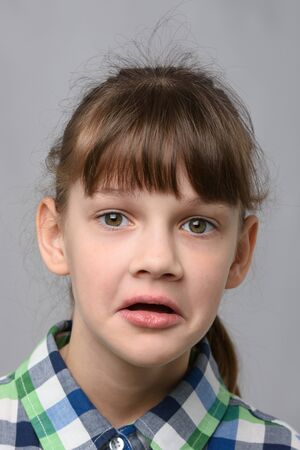 Portrait of a puzzled ten-year-old girl of European appearance, close-up