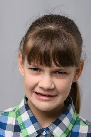 Portrait of a ten-year-old girl who is disgusted from what she saw, European appearance, closeup