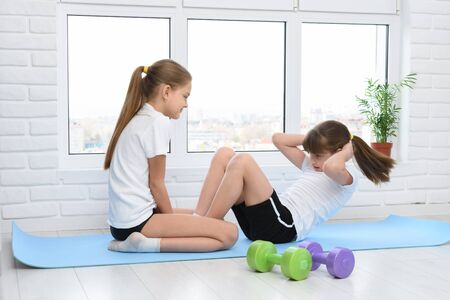 Older sister helps younger to do exercise for the press