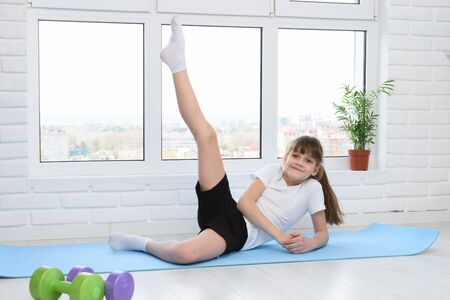 The girl lifted her leg up, doing morning exercises at home