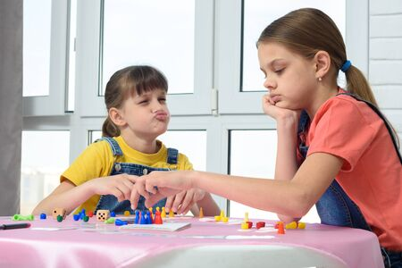 Girl playing a board game teases another girl