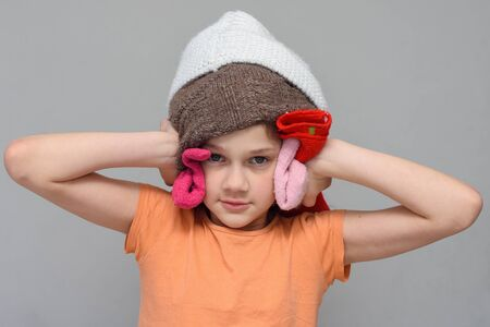 The girl put on a lot of things on her head so as not to hear loud sounds
