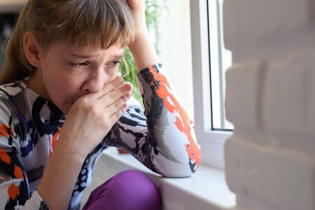 Girl weeping bitterly at the window wipes her tears with her hand