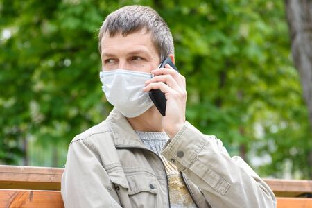 Close-up of masked man with phone on the street Stockfoto